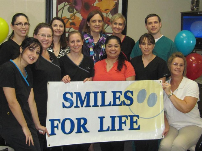Dental team holding up smiles for life sign
