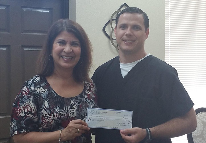 Dentist giving community organization a donation