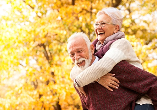 An older man carrying an older woman on his back outside while they smile and laugh, enjoying their new dental implants in San Antonio
