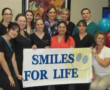 The Brice Dental team holding a Smiles for Life banner